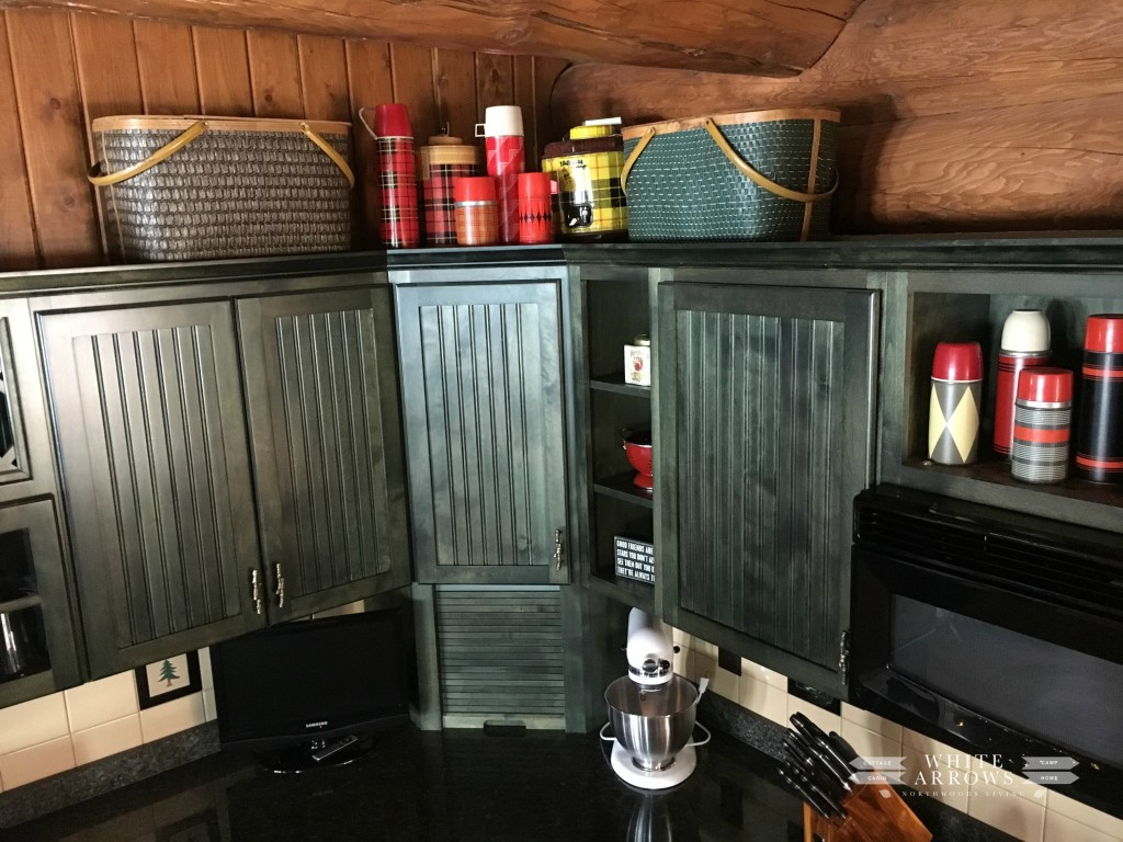 green cabinets-thermos-log home-picnic basket