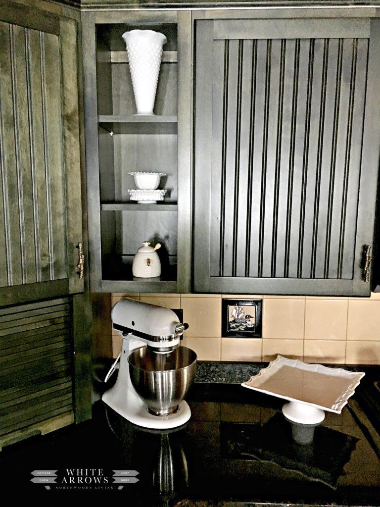 honey pot, milk glass, cake stand, kitchen aid mixer, green cabinets