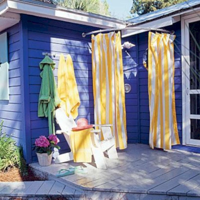 Outdoor shower with yellow and white striped curtain.
