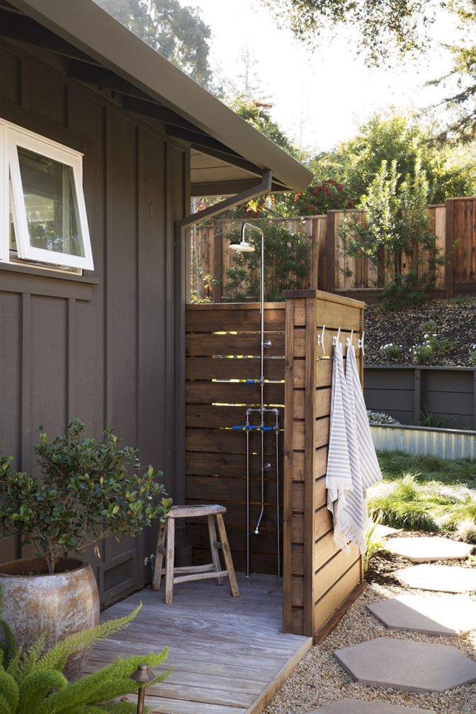Simple wooden privacy fence in L shape, partially open and shower hooks on outside.