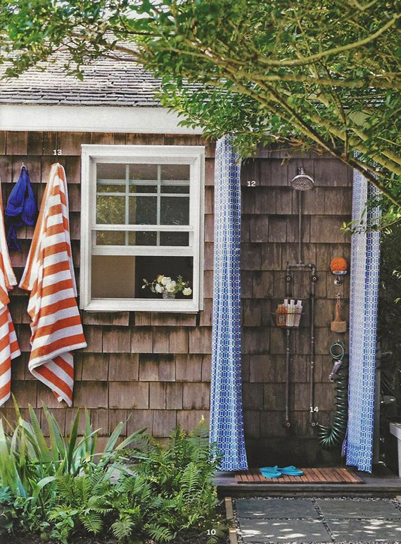 Cottage outdoor shower with blue curtain.
