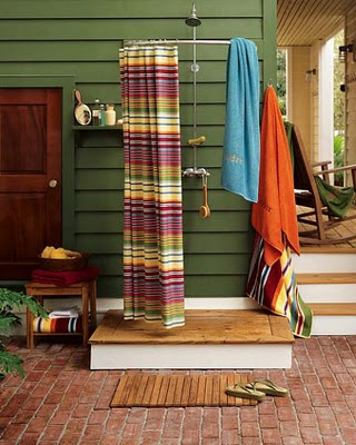 Outdoor shower with colorful striped curtain.
