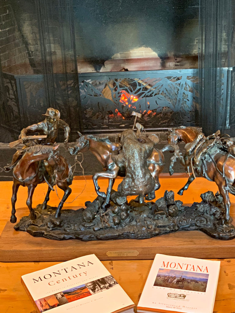 lodge fireplace and bronze cowboy statue