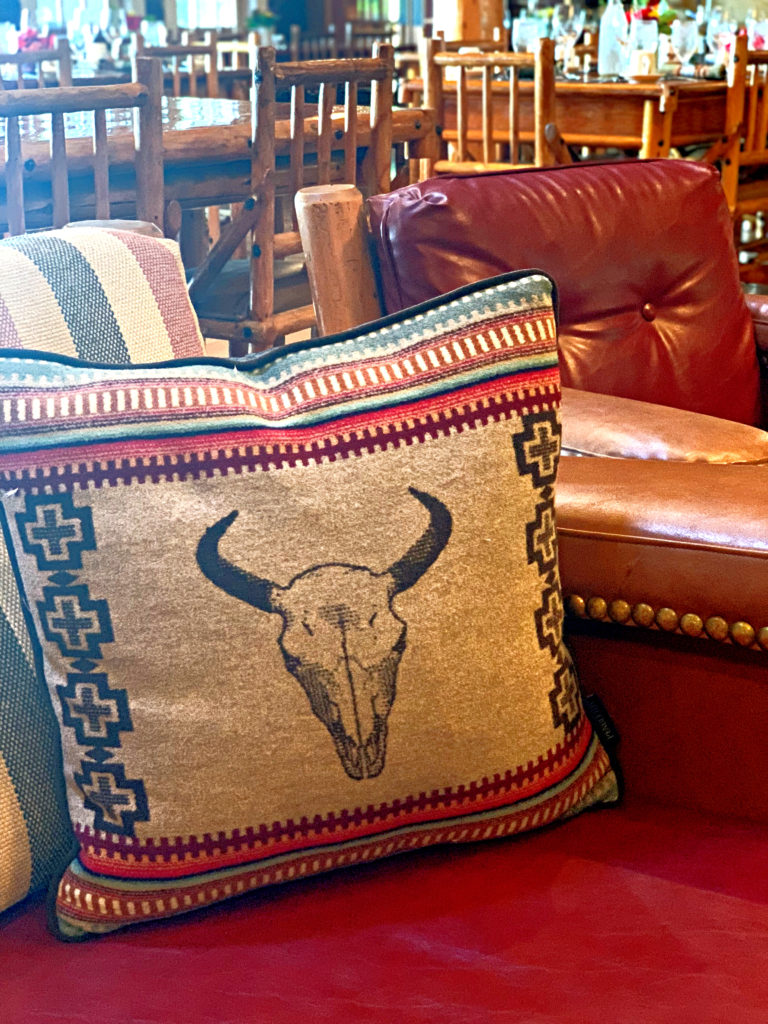 log seating with cow skull pillow