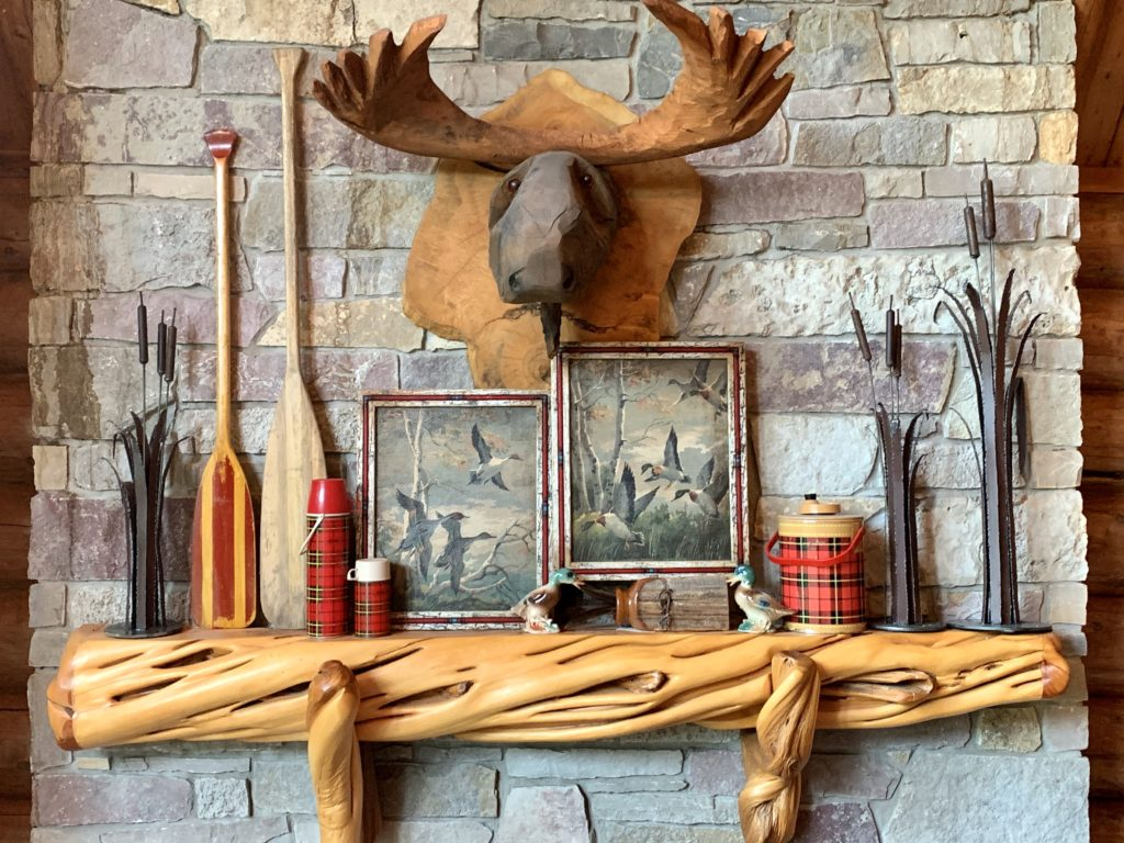 Carved wood mantel with plaid and duck hunting decor
