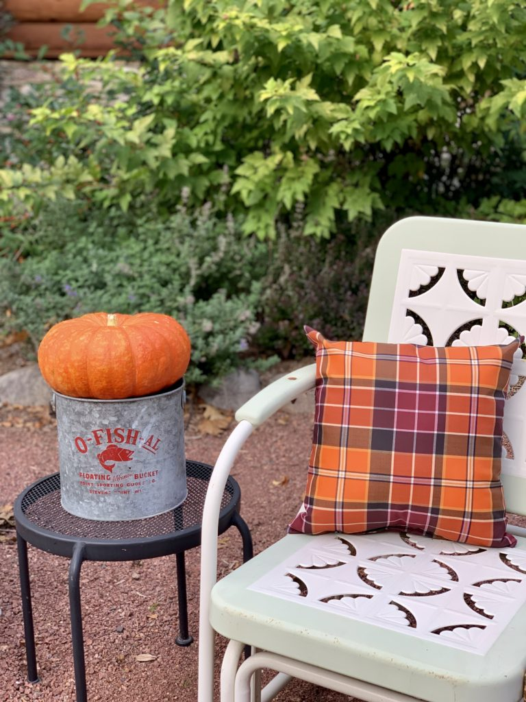 Fall plaid pillows a chair in oranges and reds and a pumpkin in a minnow bucket