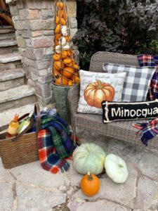 welcome bench decorated for fall with plaid blankets and pumpkins