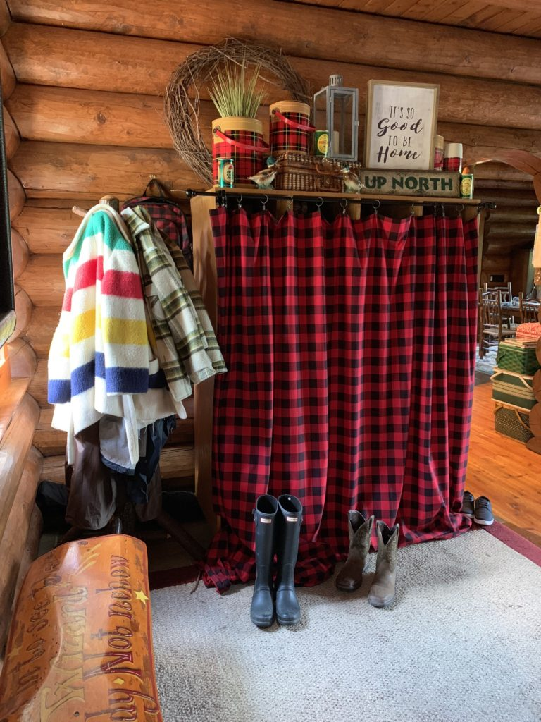 Fall Decor in entry way. Cubbies hidden behind buffalo plaid curtain.