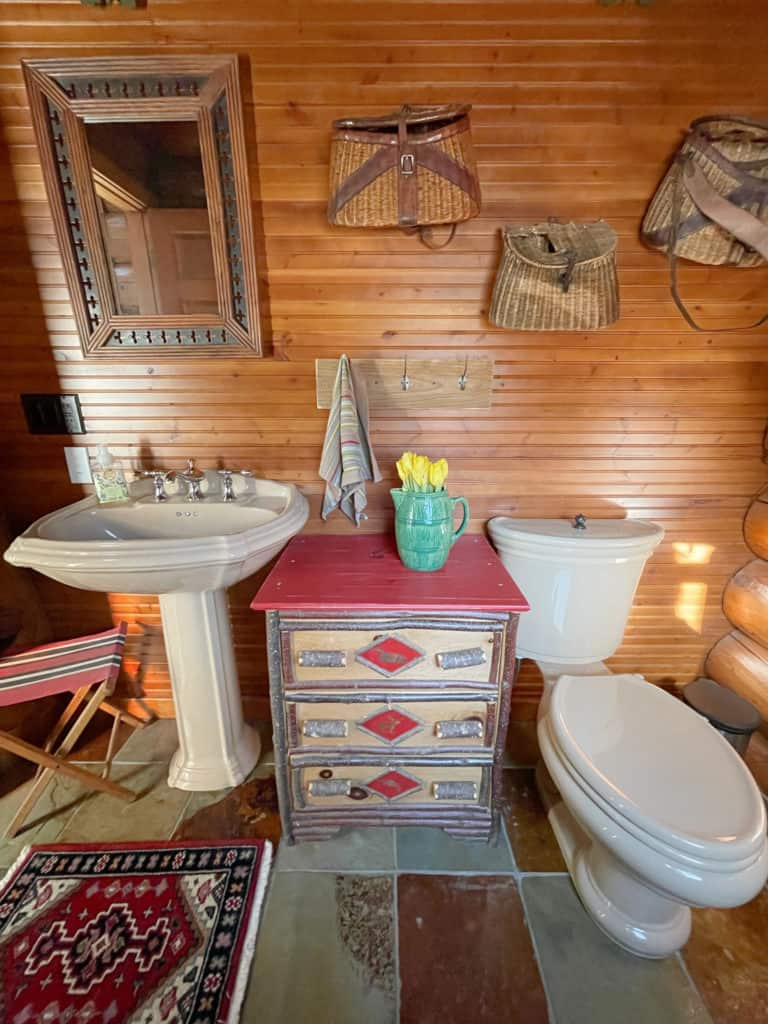 cabin bathroom with pedestal sink, dresser for storage and fishing decor