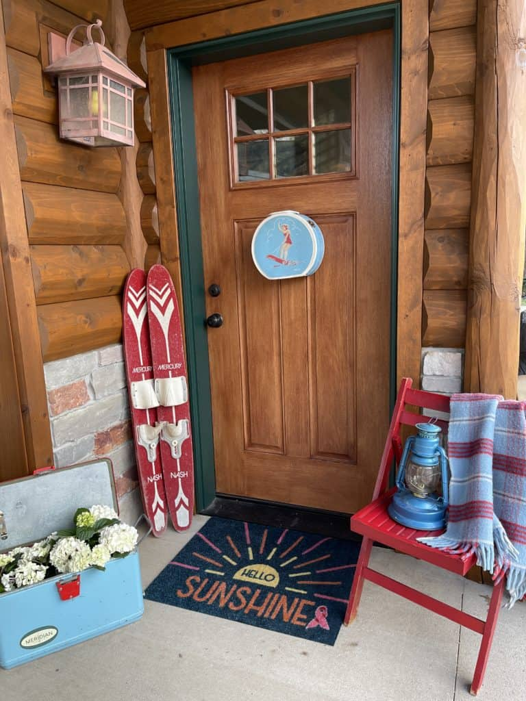lake house porch decor with vintage cooler, chair and blanket