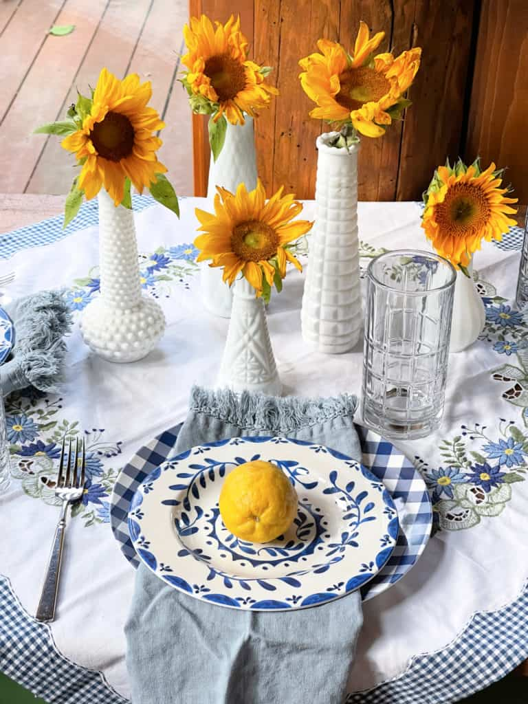 Sunroom Table set for Summer with blue and whites, vintage linens and lemons, milk glass and sunflowers